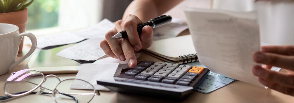 une personne qui fait ses comptes avec une calculatrice