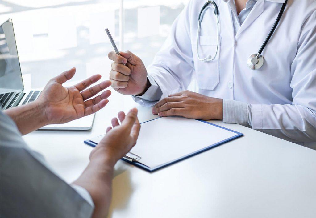 Médecin avec un stéthoscope discutant avec un patient