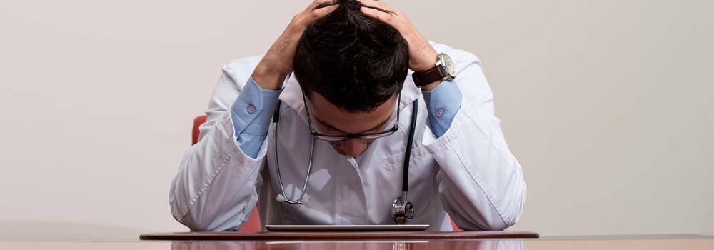 un médecin stressé la tête entre les mains